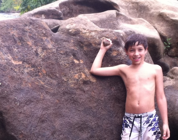 boy proud of himself holding rock removing graffiti